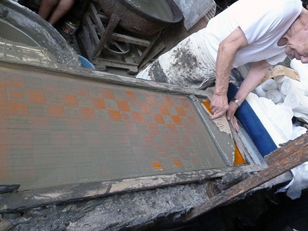 三勝・綿の白生地に型紙を重ねて防染糊-のり-を置きます