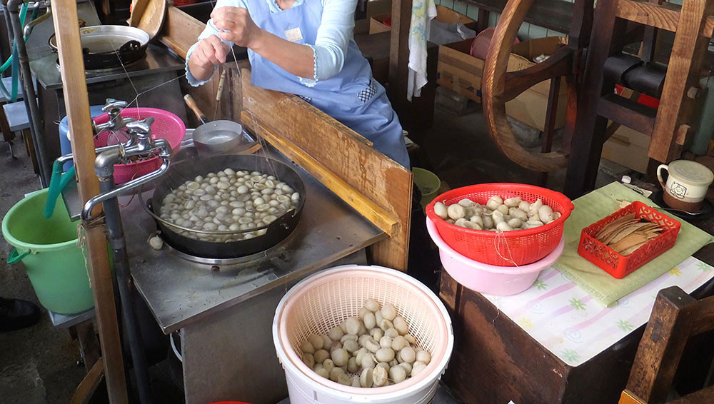 加賀・玉繭を煮込んでほぐし(手作業で80本を一束にして糸を紡ぎ出します)のべ引き
