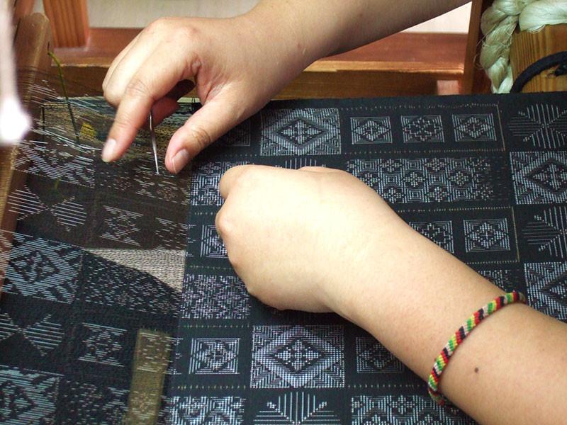 奄美・奄美大島の機織りは女性の仕事-絣目が細かいのでズレないように合わせながら織ります